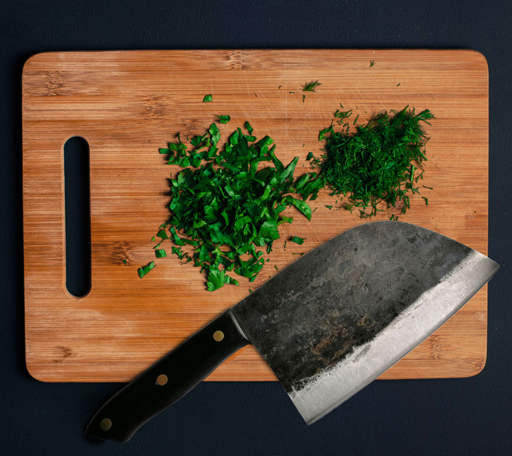 Our forged Serbian chef's knife on a cutting board with herbs