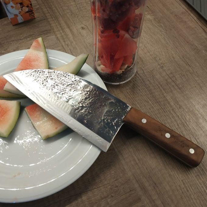 Stainless Serbian knife cutting watermelon